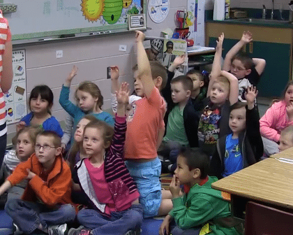 Children in a kindergarten class eagerly raising their hands ready to ask questions.